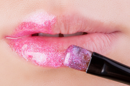 lip gloss: Pink glitter on natural lips. Close-up . Great idea for advertising lip gloss.