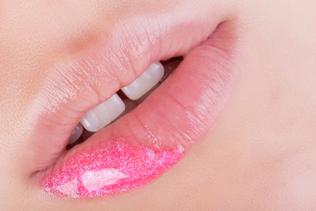 gloss: Pink glitter on natural lips. Close-up . Great idea for advertising lip gloss.