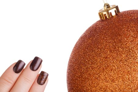 christmas toy: Beautiful brown nails and Christmas toy. Stock Photo