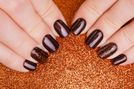beautiful nails: Beautiful brown nails and Christmas toy. Stock Photo