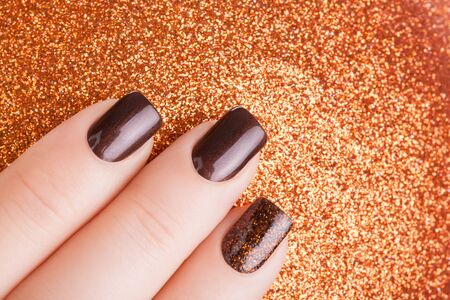 nail lacquer: Beautiful brown nails and Christmas toy. Stock Photo
