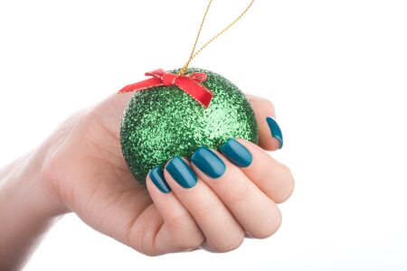 christmas manicure: Beautiful green nails of Christmas toy.