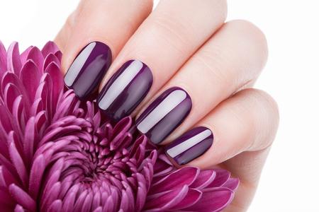 manicura: uñas rojas hermosas y flor de primer plano.