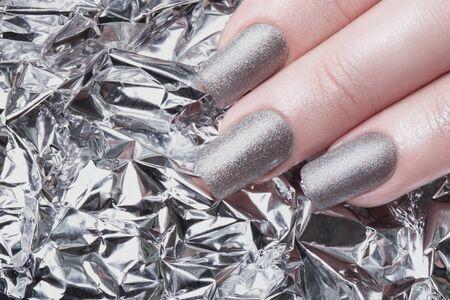 cosmetic lacquer: Very beautiful silver metallic nails closeup. Stock Photo