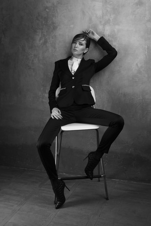 stool: Fashionable girl in a chic classic suit.