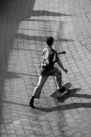 Young guys in stylish clothes ride a skateboard in the park.