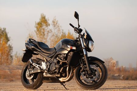 One black motorcycle in the desert in autumn time. Banque d'images