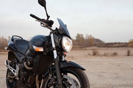 One black motorcycle in the desert in the fall.