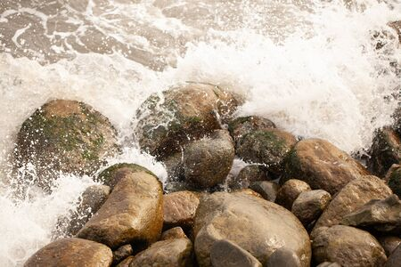 The sea beats against stones and splashes fly.