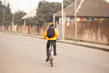 A country boy in a yellow sweater rides an old bicycle on a rural road. Stock Photo