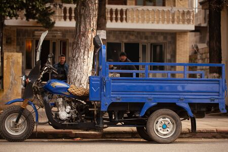 Unusual old tricycle rides on the road.
