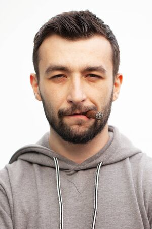 Handsome stylish man smokes a cigar.
