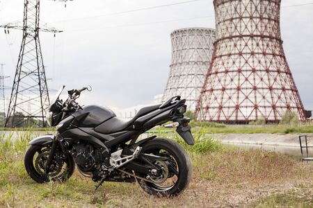 Sports black motorcycle near the power plant.