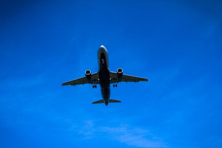 Jet airplane flying overhead close-up on a blue sky background