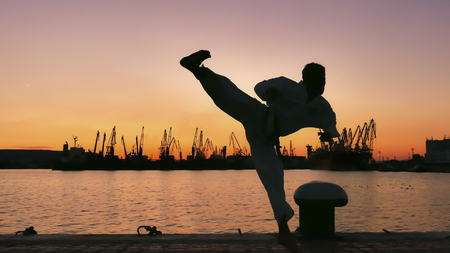 martial artist training alone on the sea pier, practicing his moves on sunset and port cranes background.