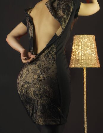 Girl takes off a dress in the studio on a black background. Sexual undressing. Rear view. Seduction Standard-Bild