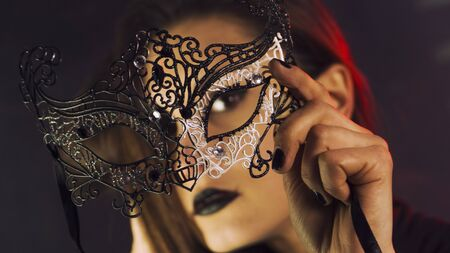 Beauty model wearing venetian masquerade carnival mask. Masquerade party. Luxurious glamor portrait, femme fatale in carnival mask. Black lipstick