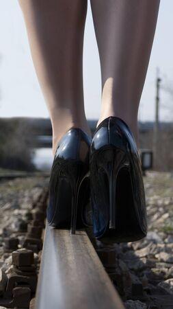 Unrecognized woman walking along in high heels on the railway track. Reklamní fotografie