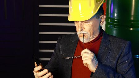 Old senior oilman in yellow helmet making calculations, oil barrels on background. Oil price falling conception.