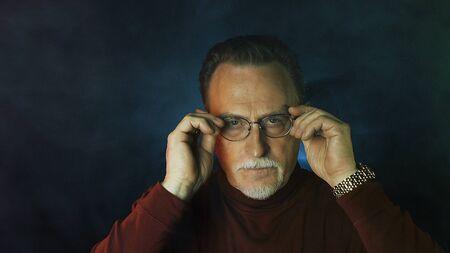 Mature gentleman on dark background. Medium shot portrait elderly elegant man. Handsome gray haired old businessman in glasses. Archivio Fotografico