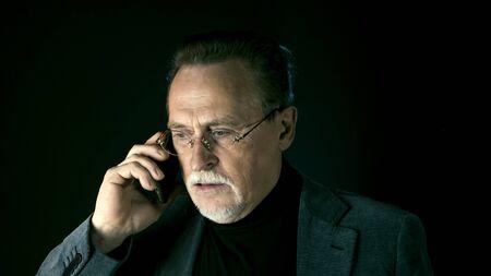 Mature gentleman talking on a smartphone. Medium shot portrait elderly elegant man with phone on dark background. Handsome gray haired old businessman in glasses.