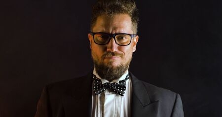 Handsome man in suit on black background. Portrait of elegance gentleman with glasses. Luxury lifestyle. Portrait of adult spy wearing trendy suit in studio.