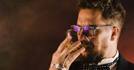 Handsome man in suit drinking champagne on black background. Portrait of elegance gentleman with glasses. Confident adult man in suit holding glass of champagne in studio. Luxury party.
