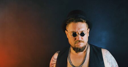 Portrait of athletic guy with a tattoo poses with a baseball-bat in dark studio. Cool mafia gangster in sunglasses and cylinder hat. Bearded bouncer with baseball-bat and sunglasses.