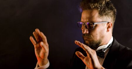 Emotional conductor on dark background. Man conducting an orchestra. Archivio Fotografico