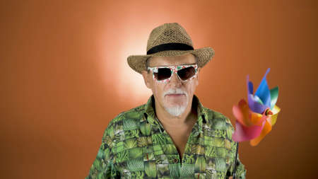 Studio portrait of the joyful elderly tourist in a straw hat and hawaiian shirt on colored backgrounds. Peoples emotion. Happy and funny celebrating people. Banco de Imagens