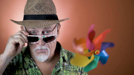 Studio portrait of the crazy grandfather on colored backgrounds. Peoples emotion. Happy and funny celebrating people. Banco de Imagens