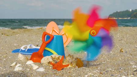 Children's beach toys, on sand beach in summer day. Beach kid's toys on the white sand. Kid's summer vacation concept.