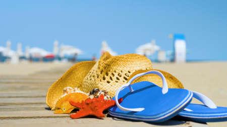 Beautiful summer holiday beach background with straw hat and seashells. Summer concept with accessories on the sandy beach Banco de Imagens