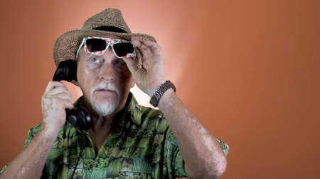 Portrait of a joyful elderly man in a straw hat and Hawaiian shirt speaking on the retro phone on colored backgrounds. People's emotions. Happy and funny people.