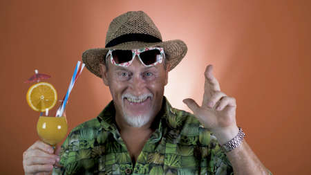 Portrait of a joyful elderly tourist in a straw hat and hawaiian shirt holding a tropical orange juice use on a colored background. Banco de Imagens