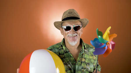 Portrait of a joyful elderly tourist in a straw hat and hawaiian shirt holding a beach ball on a colored background. Vacation at sea. Banco de Imagens