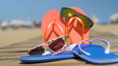 Starfish, seashells and flip-flops on wooden board. Summer holiday background, vacation and travel items. Summer concept with accessories on the sandy beach Banco de Imagens