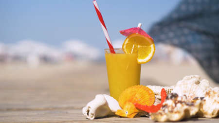 Fresh orange juice, starfish and seashells on wooden board. Summer holiday background, vacation and travel items. Summer concept with accessories on the sandy beach.