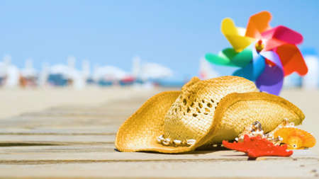 Beautiful summer holiday beach background with straw hat and seashells. Summer concept with accessories on the sandy beach Standard-Bild