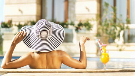 Beautiful brunette woman with the sunglasses and summer hat relaxing in the swimming pool. Elegant lady drinks a summer cocktail on vacation at a luxury resort. Luxury lifestyle. Holidays, wellness