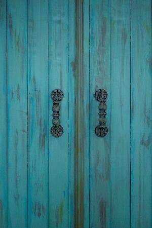 Wooden blue door with metal old door-handle. Retro style. Stock Photo