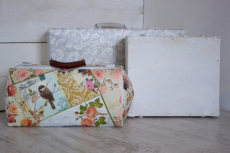 secondhand: Three retro suitcases on a white wooden background.
