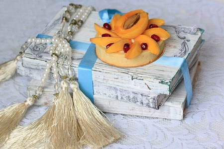Appetizing tartlet with a apricot is lying on a pile of books. Sweet dishes.