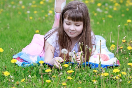 Cheerful little girl lying on a beautiful coverlet in the grass. Carefree childhood.