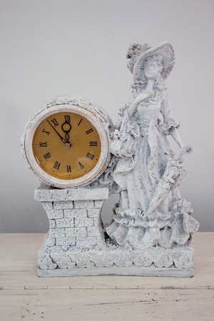Clock with a woman statue is standing on a wooden table. Beautiful interior.
