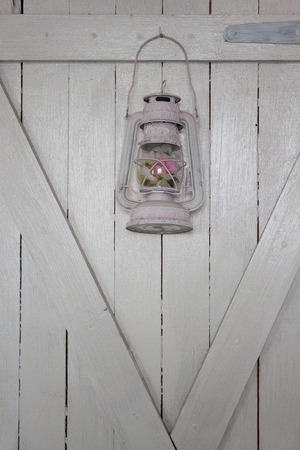 Old pendant lamp is hanging on a white wooden door. Retro style.