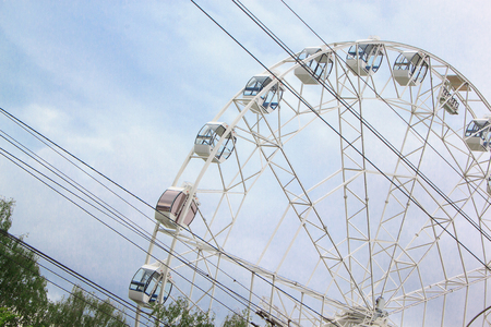 round: Large ferris wheel is spinning in an amusement park.