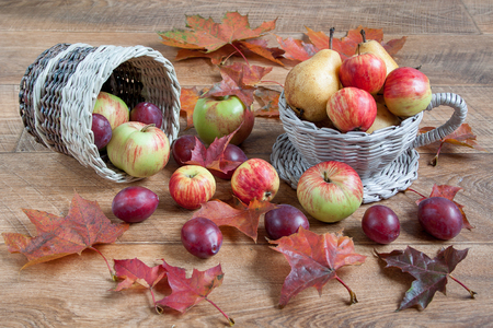 basketry: Fruits and autumn leaves are lying on a wooden table and in a wicker baskets. Gifts of nature Stock Photo