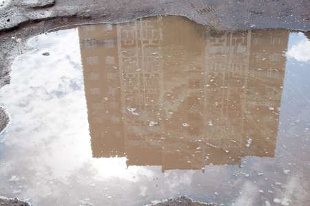 The bad asphalted road with a big pothole filled with water. Dangerous destroyed roadbed. Mirror reflection of a building in the water.