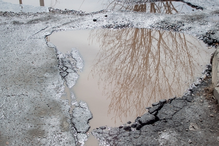 The bad asphalted road with a big pothole filled with water. Dangerous destroyed roadbed. Stock Photo
